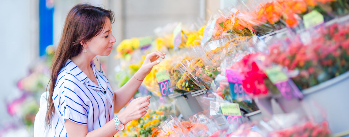A woman looking at a flower shop's display and price tags